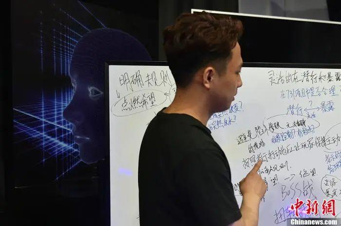 周新宇向记者讲述他对该抗战题材教育类游戏的设想。中新网记者 李骏 摄