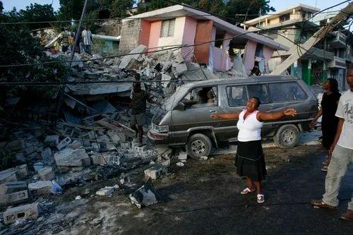 2010年1月13日,在发生地震的海地首都太子港,一名女子在被震毁的房屋旁哭泣。新华社/路透?