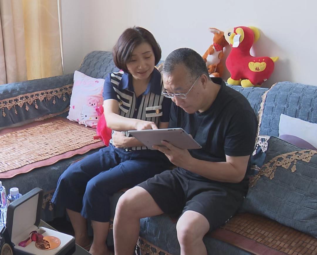 章瑾父母在家中翻看女儿的照片,他们已有两年多未见到女儿了。