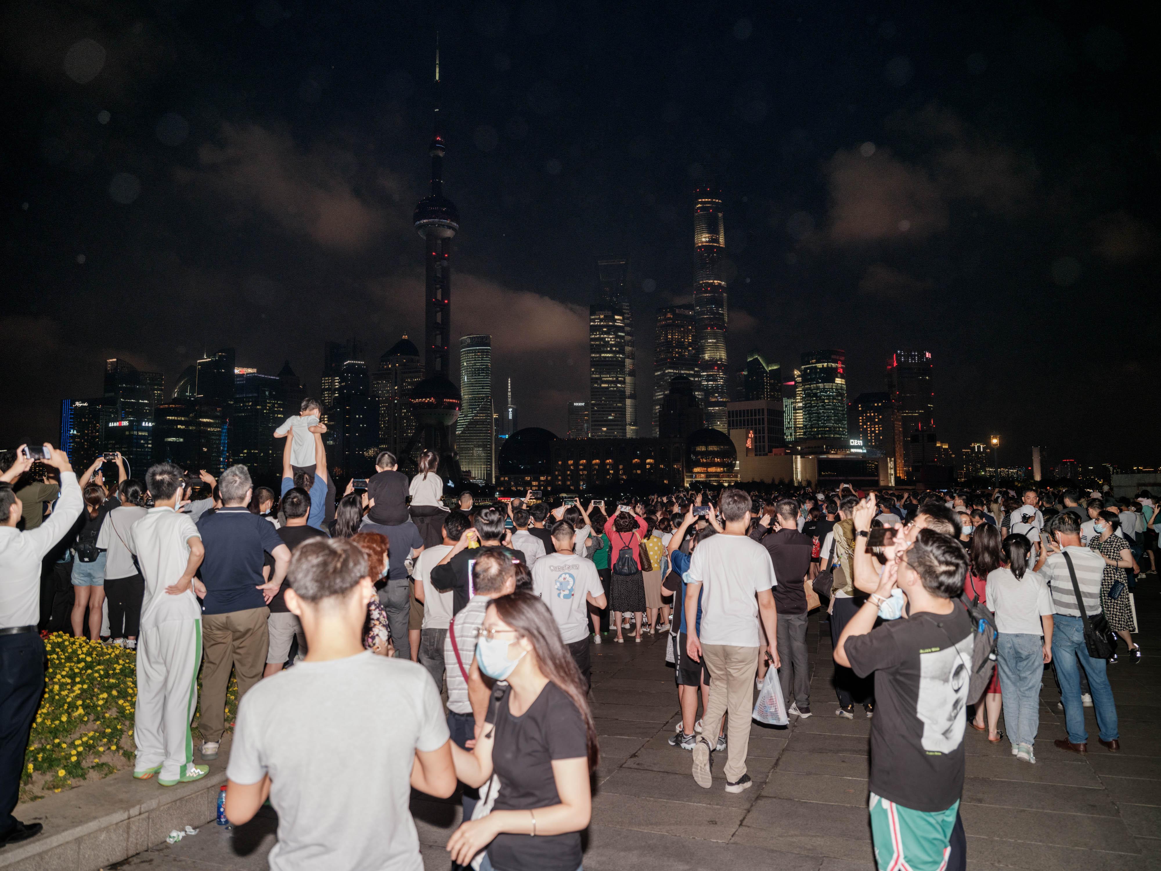 人们从四面八方来看灯光秀,孩子和手机都被举得高高。