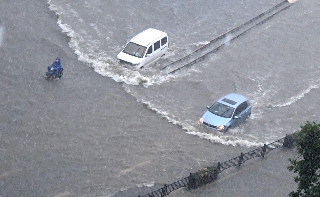 7月20日,车辆在郑州街头涉水前行。 新华社 图