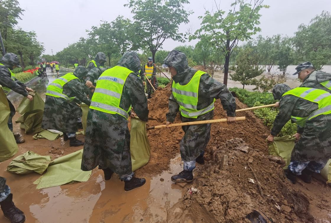 7月21日,驻扎在郑州的中部战区空军某部官兵在贾鲁河中牟段装填沙袋加固堤坝(手机拍摄)。新华社 图