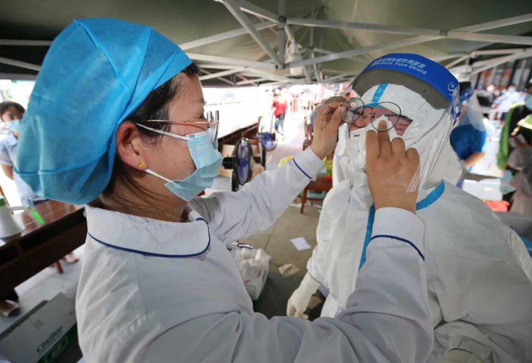 江宁区核酸检测点,工作人员在帮助身着防护服的医护人员擦汗。