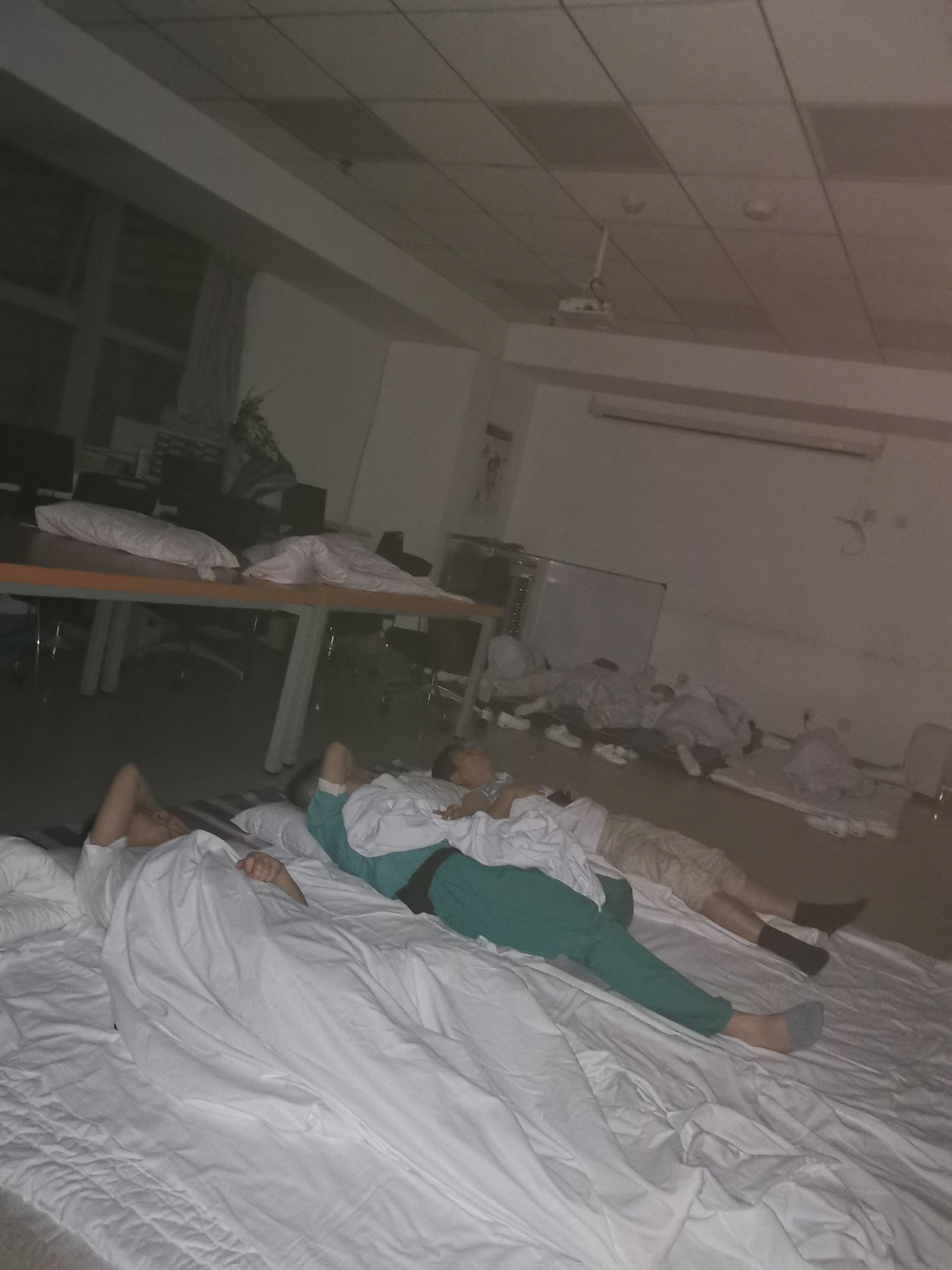 7月20日晚,郑大一附院停电后,方泽民(中)与同事在医院打地铺。受访者供图