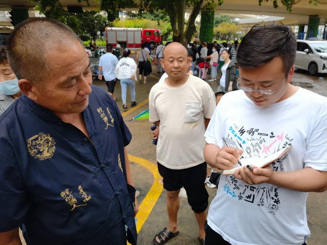 7月21日,人民日报社记者毕京津(右)在郑大一附院采访患者转运。