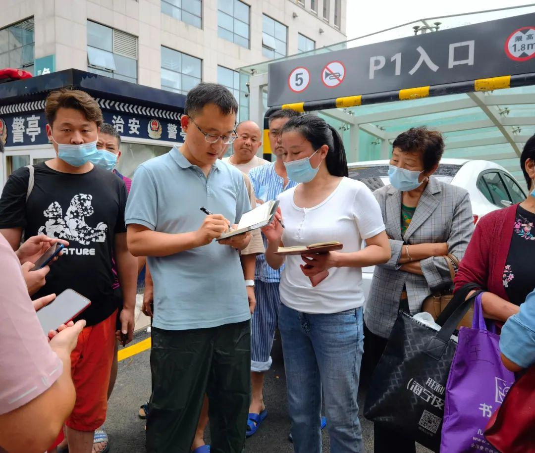 7月21日,人民日报社记者马跃峰(左二)在郑大一附院采访患者转运。