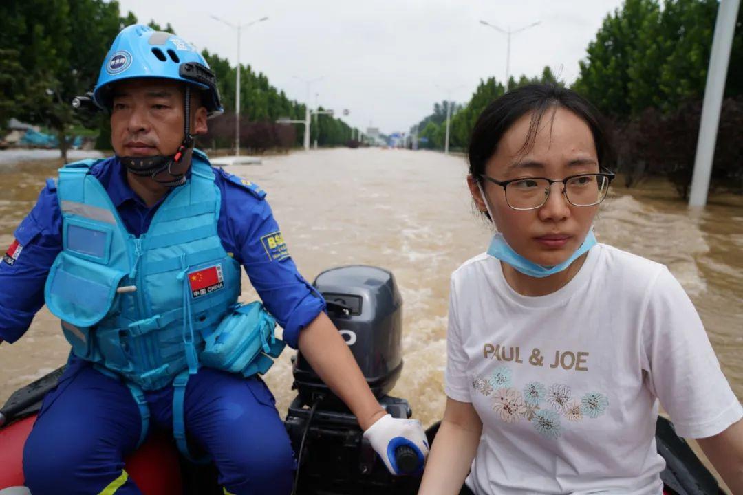 7月22日,新华社记者袁月明(右)乘冲锋舟前往郑州阜外华中医院采访。