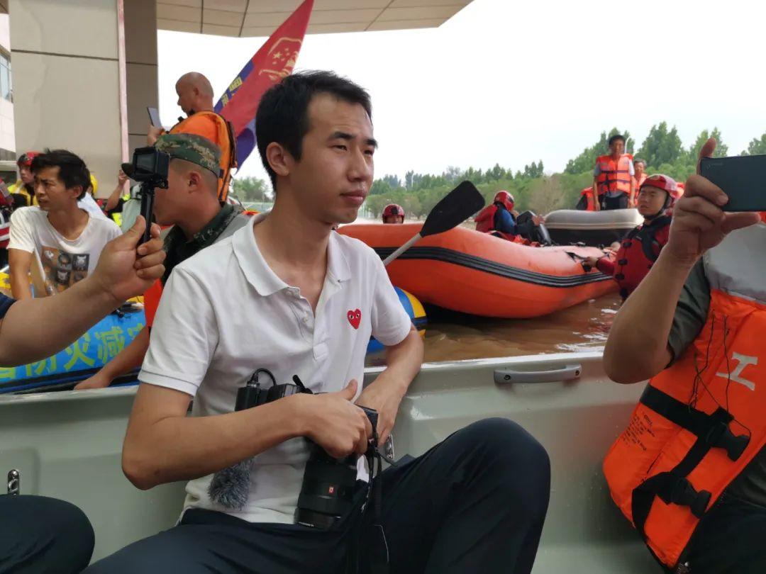 7月22日,新华社记者姚竣译乘冲锋舟前往郑州阜外华中医院采访。