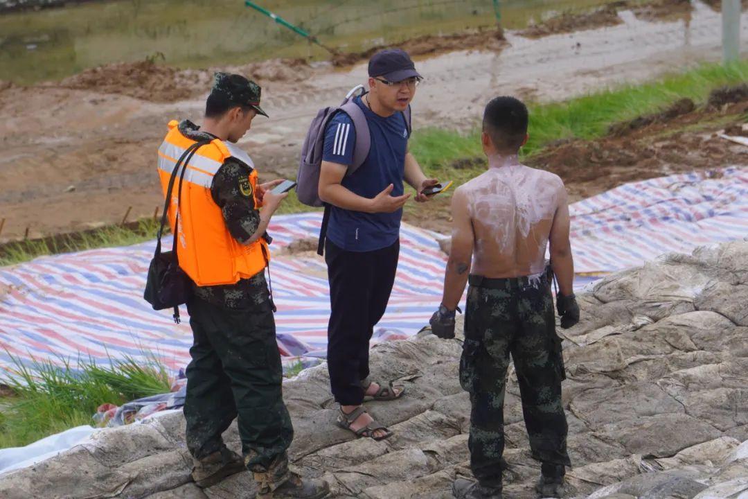 7月21日,中新社河南分社记者李贵刚(中)在新密五星水库采访。