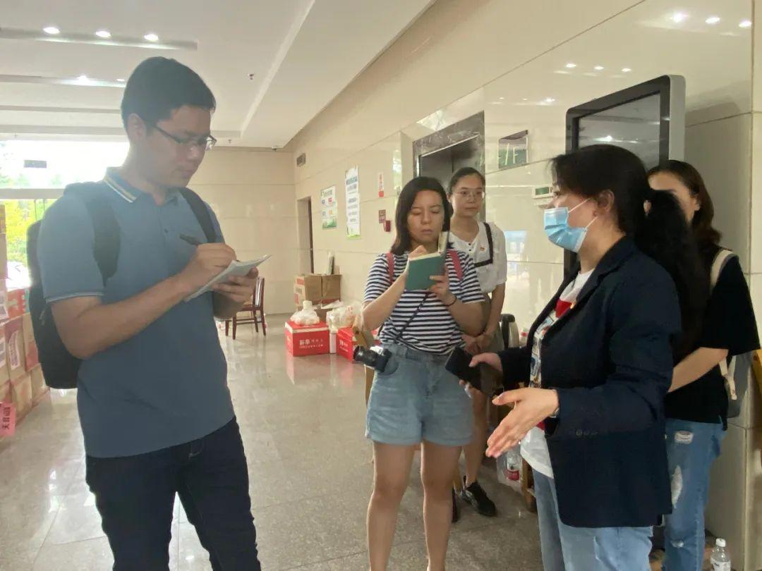 7月22日,中国妇女报社记者田梦迪(左二)、韩亚聪(左一)在郑州市儿童福利院转移安置点采访工作人员。