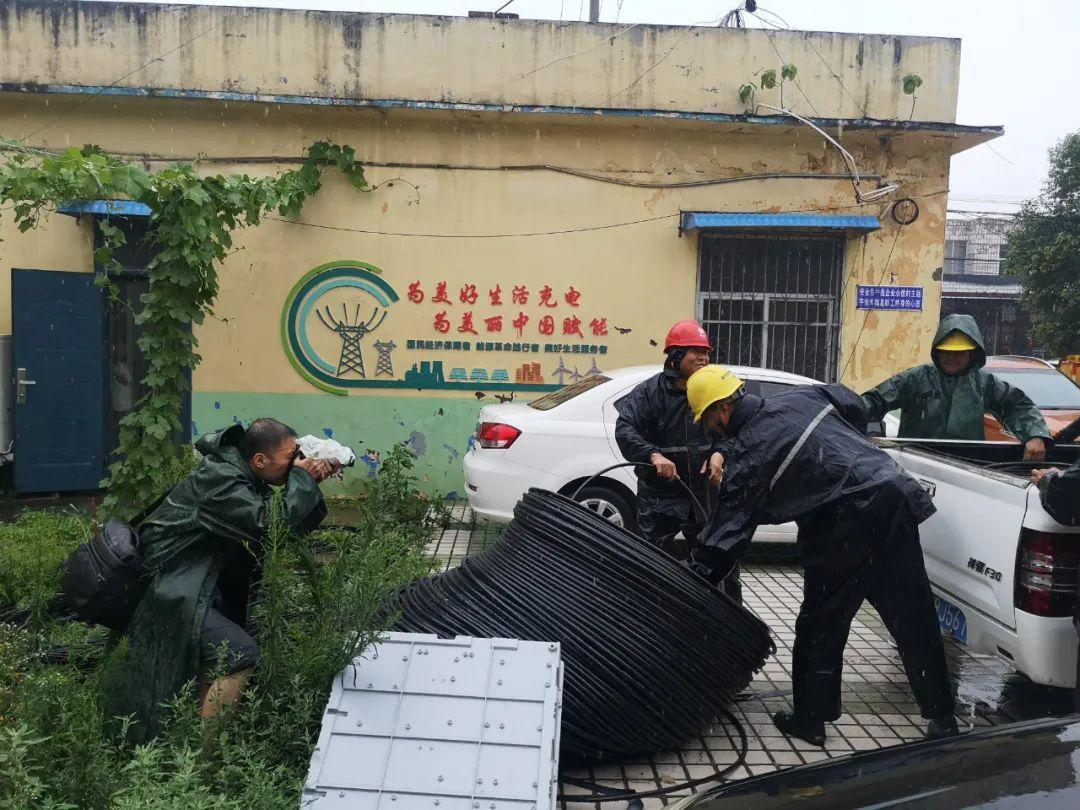 7月20日,国家电网报社通讯员郭奇(左一)在河南新乡采访正在紧急架设照明线路的工作人员。张文哲 摄