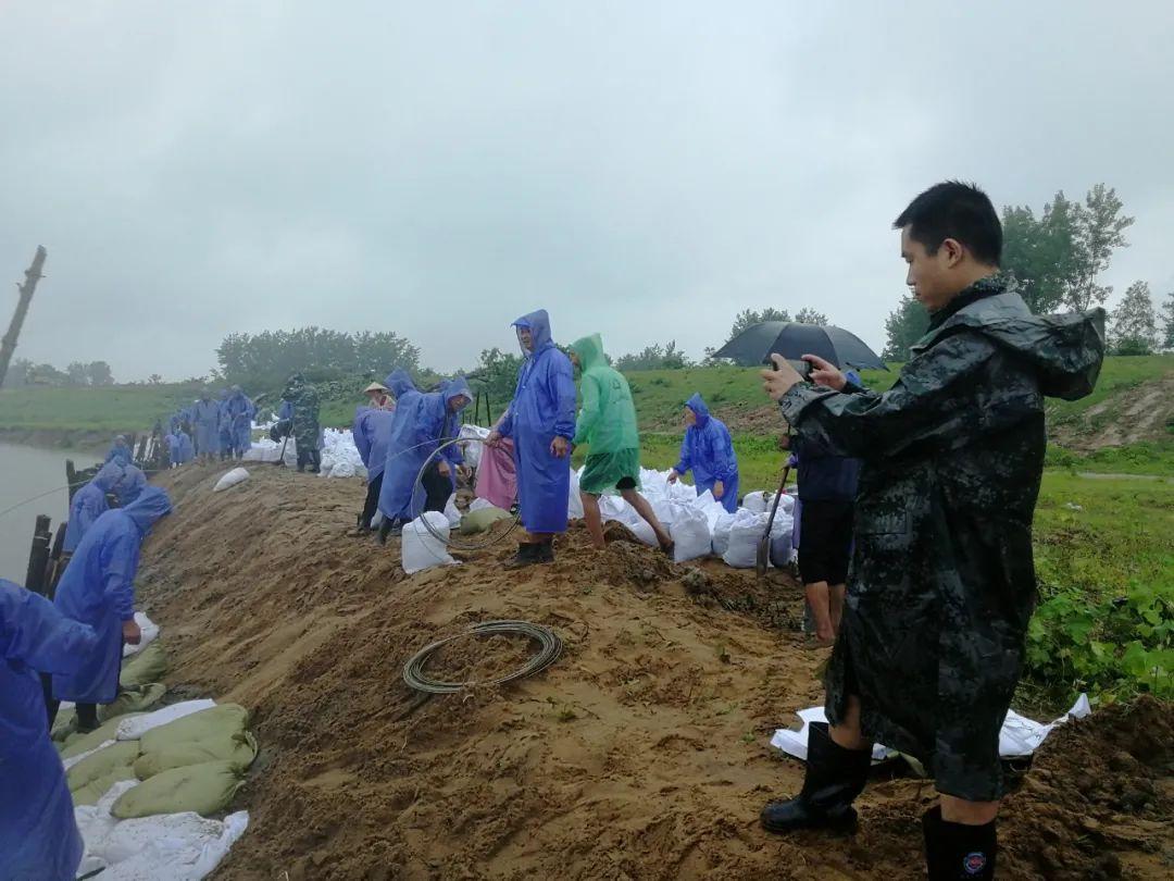 7月5日,河南日报社记者郭北晨(右)在固始采访防汛抢险。