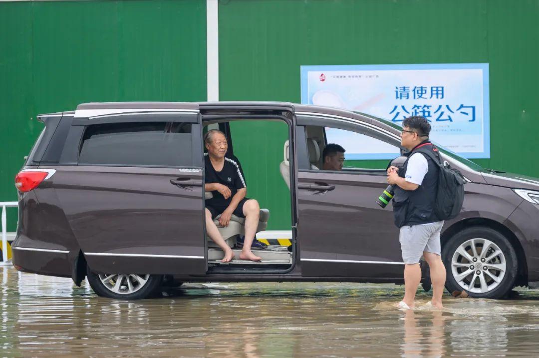 7月21日,河南商报社记者侯建勋在郑州东三环商都路积水路段进行采访。