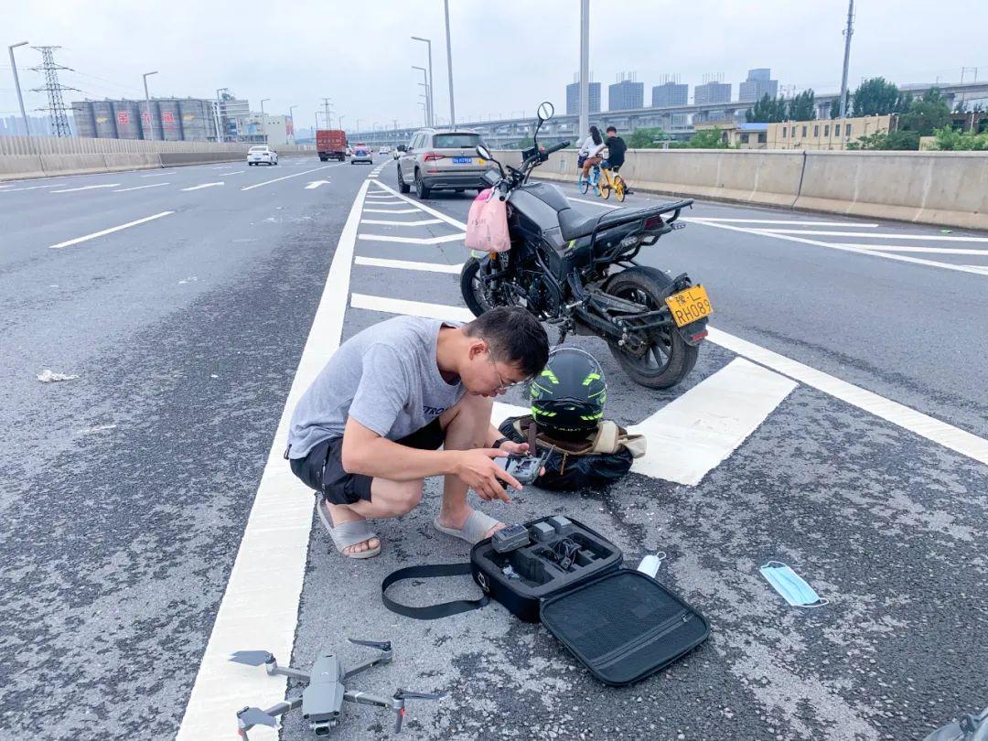 7月21日,河南商报社记者宋亚猛在高架桥上操控无人机进行积水区域航拍。