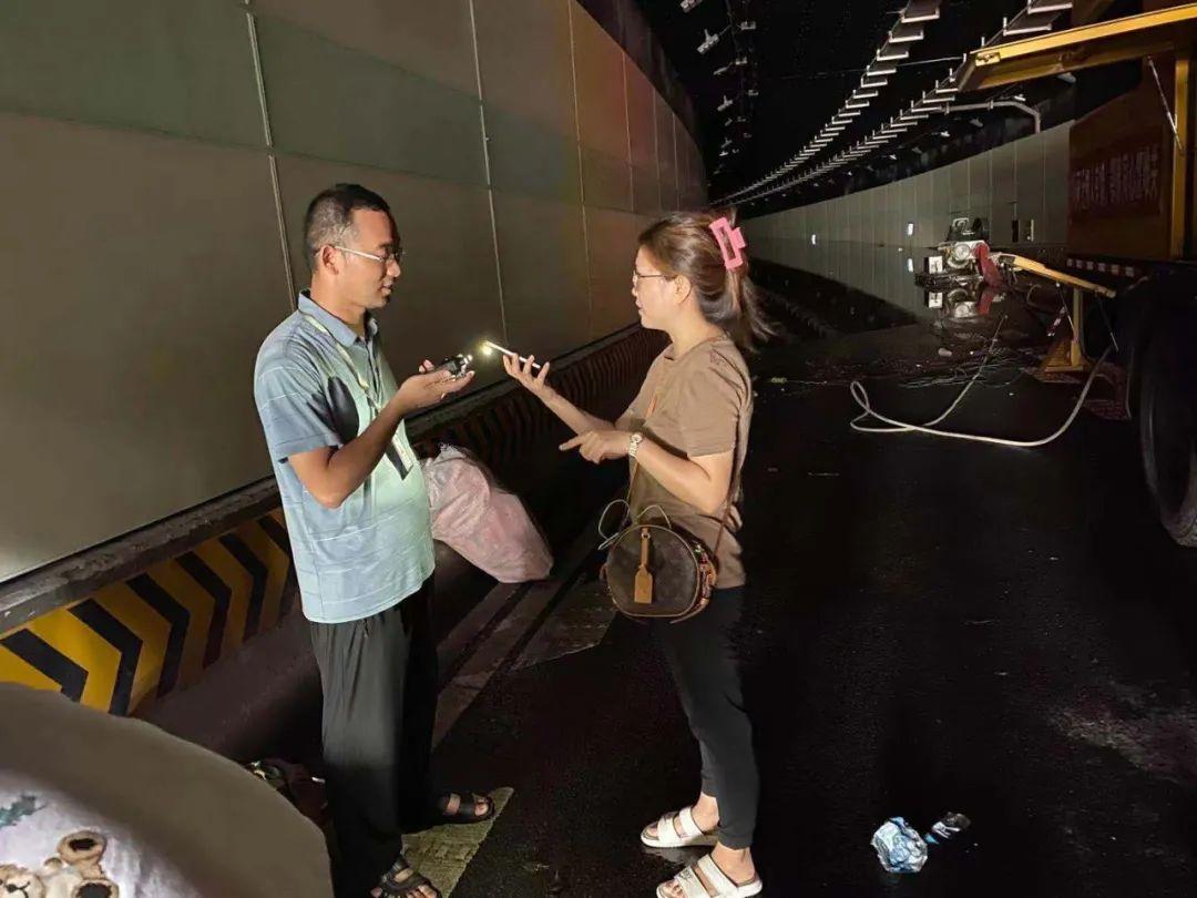 郑州广播电视台记者李欣洁(右)在郑州纬四路下穿隧道采访。