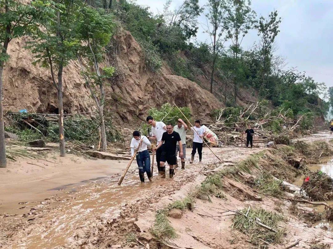 7月22日,澎湃新闻记者薛莎莎(前一)跟随救援队伍在郑州市二七区樱桃沟景区管委会桐树湾社区附近村庄采访报道。