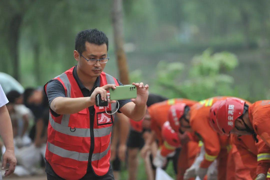 7月21日,大众网·海报新闻记者贺辉在河南开封市区碧水河决口现场,采访拍摄山东消防队队员用沙袋封堵决口处。