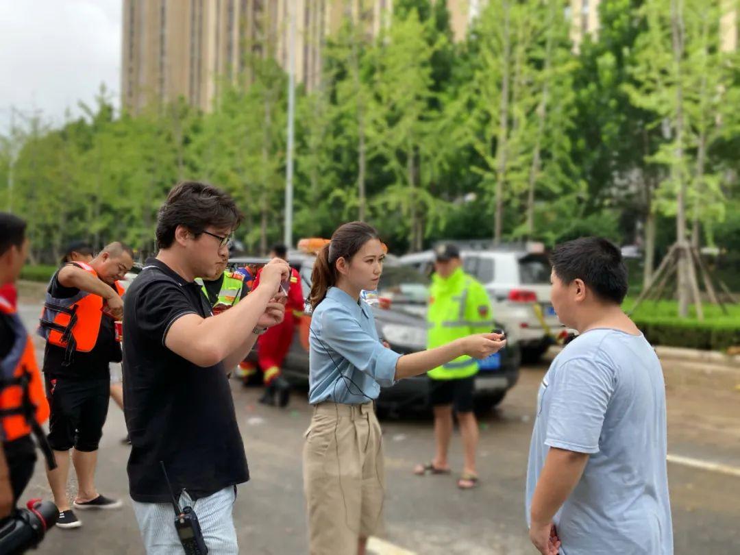 7月22日,闪电新闻记者王雨(中)、黄健荣(左)在河南郑州采访。