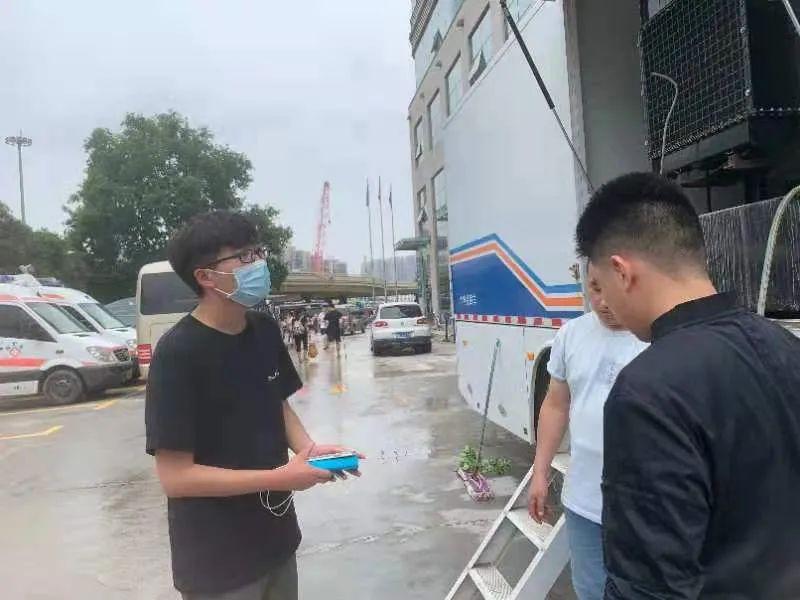 7月22日,湖北日报传媒集团极目新闻记者姚岗(左)在郑州街头采访。