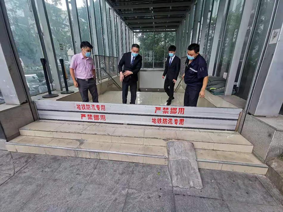静安寺地铁站工作人员在出入口处放置防汛板。
