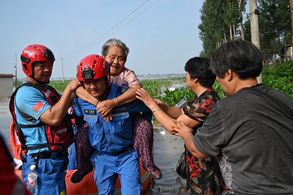 2021年7月23日,鹤壁市新镇镇路桥附近,救援队将被困居民转移至安全区域。