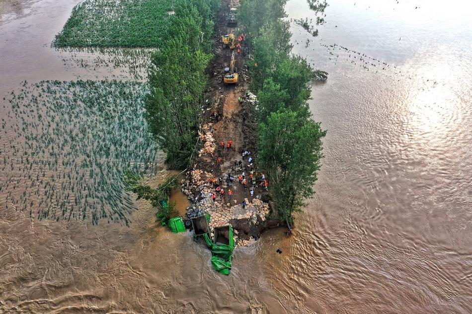 2021年7月23日,鹤壁市新镇镇路桥附近决口处,已填入数车石头及多辆大卡车。