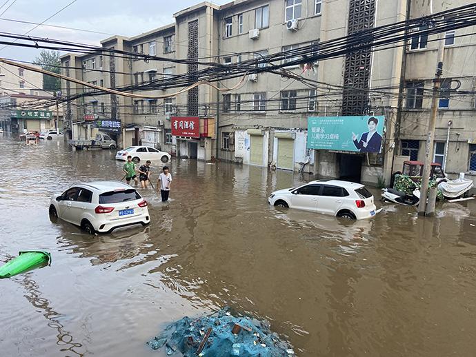 """洪水将卫辉市城区低洼处淹没,形成一个个""""孤岛"""",不少市民外出只能蹚水。"""