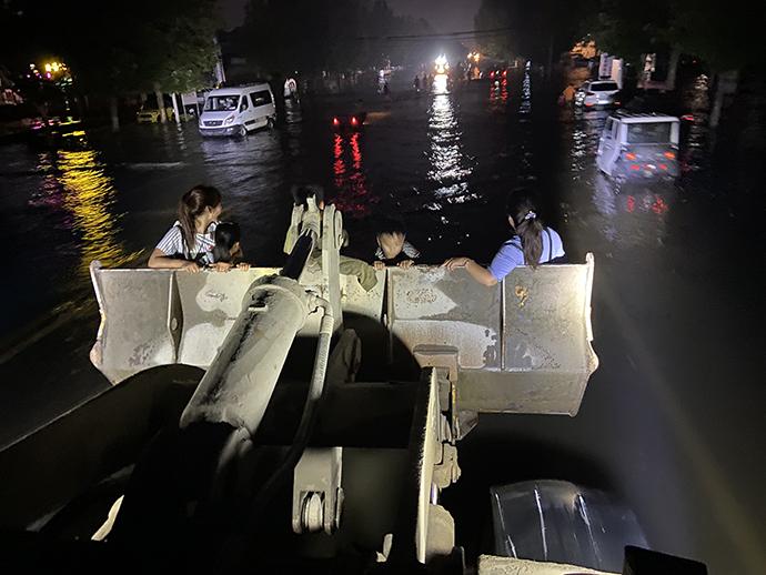 在积水严重的情况下,装载车成为最好的转移工具。夜色中,依稀可见水中等待转移的群众。