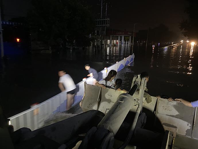 两名在水中前行的市民看到装载车过来,趴在路栏上躲避波浪。