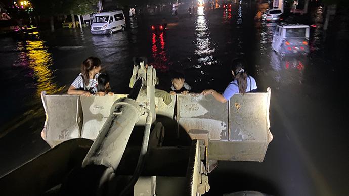 特写丨洪水围困卫辉:无奈的装载车司机和摸黑蹚水转移的市民
