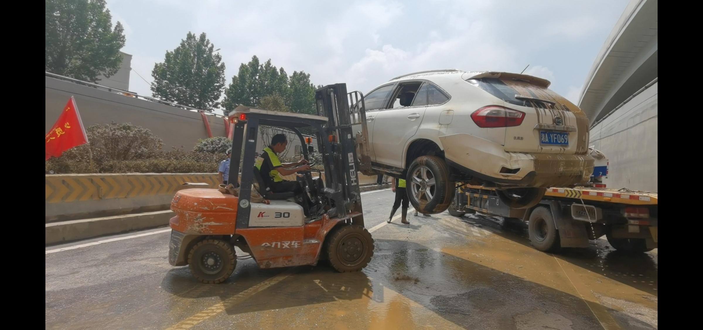 :7月24日上午11点,抢险人员正在将车辆叉到拖车上。