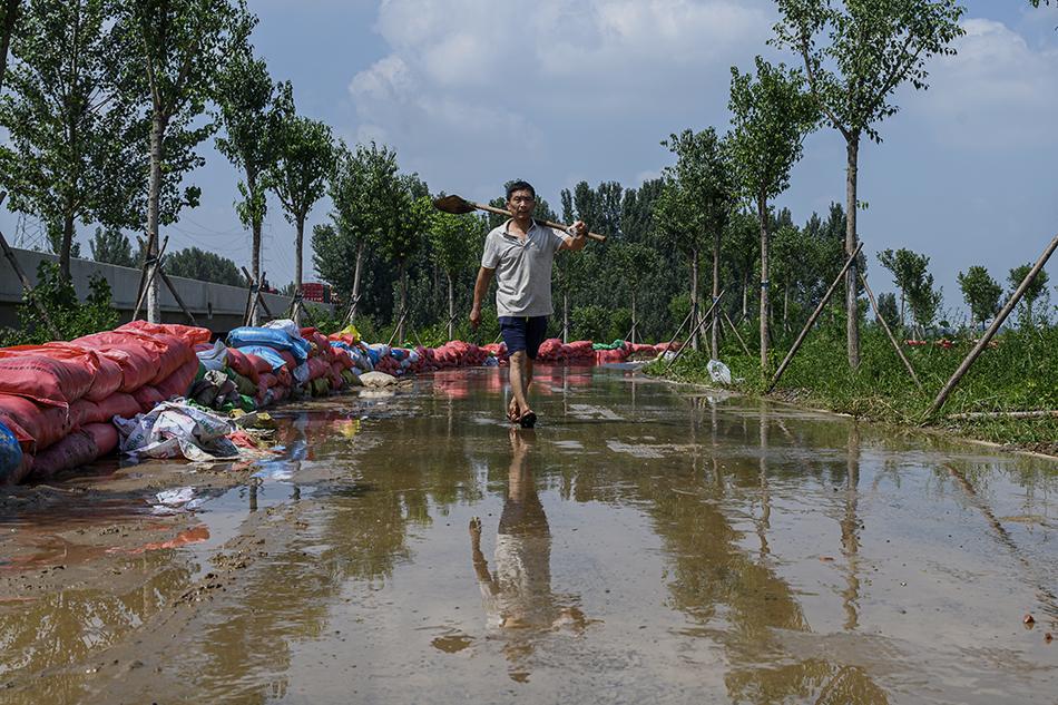 2021年7月24日,河南新乡市卫辉市汲城村,村民孟先生前往卫河边填灌沙袋。