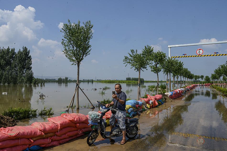 2021年7月24日,河南新乡市牧野大桥下,一名附近居民在卫河边寻找手机信号。
