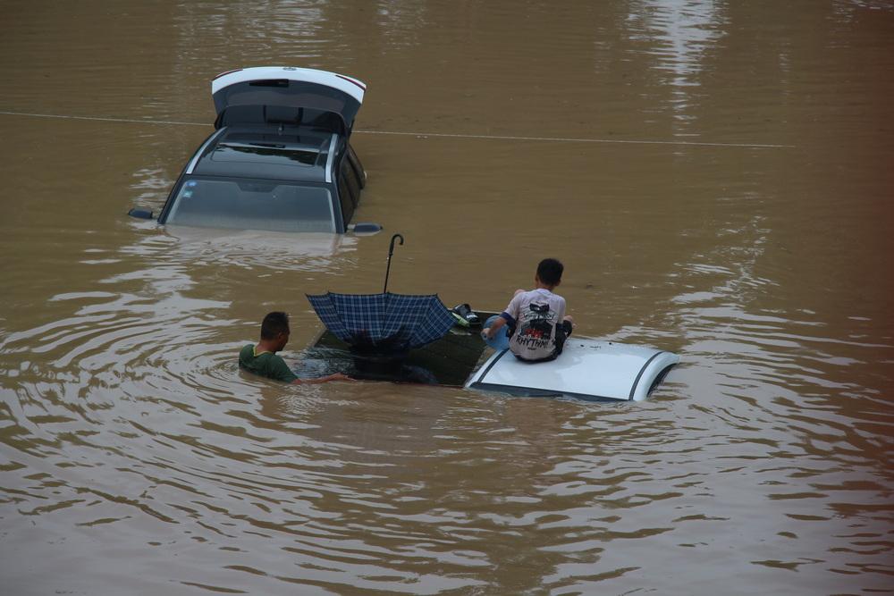 """受困人员将雨伞倒放在水中当作""""购物筐""""。 本文图片 受访者提供"""