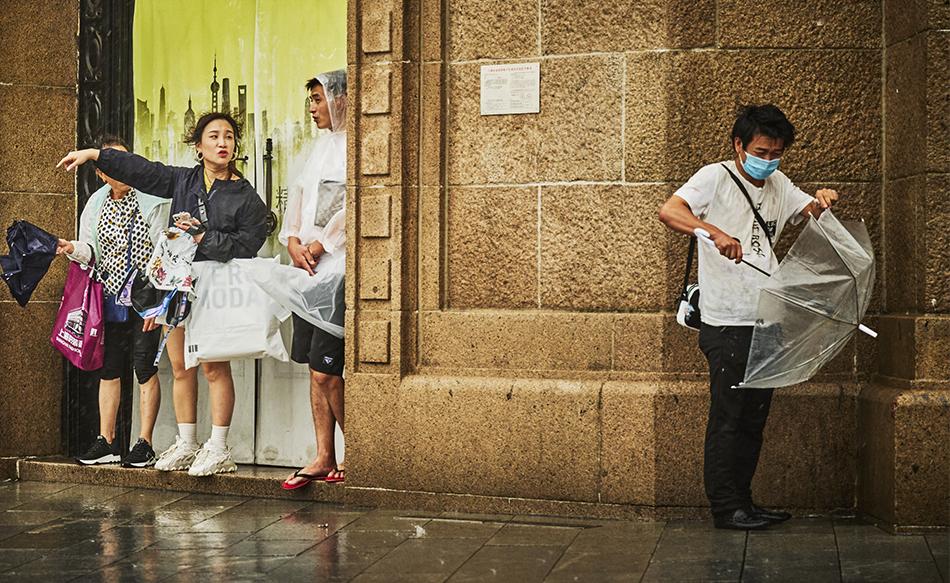 2021年7月25日17时许,上海南京东路,在墙角躲雨的行人试图修伞。