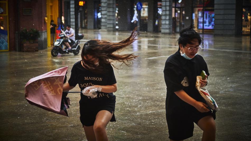 2021年7月25日17时许,上海南京东路,行人在风雨中举步维艰。