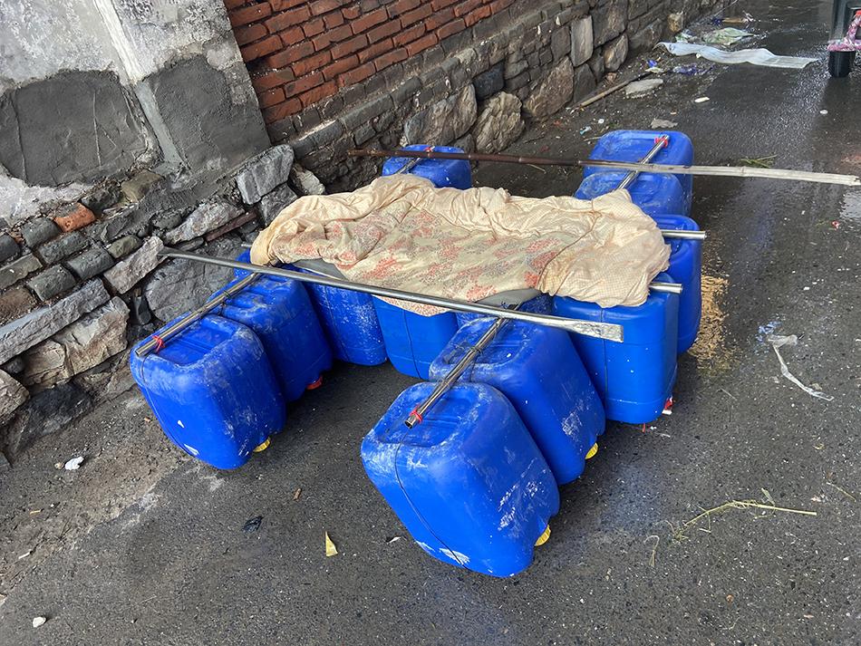 """被洪水围困的群众用塑料桶自制的""""船""""。"""