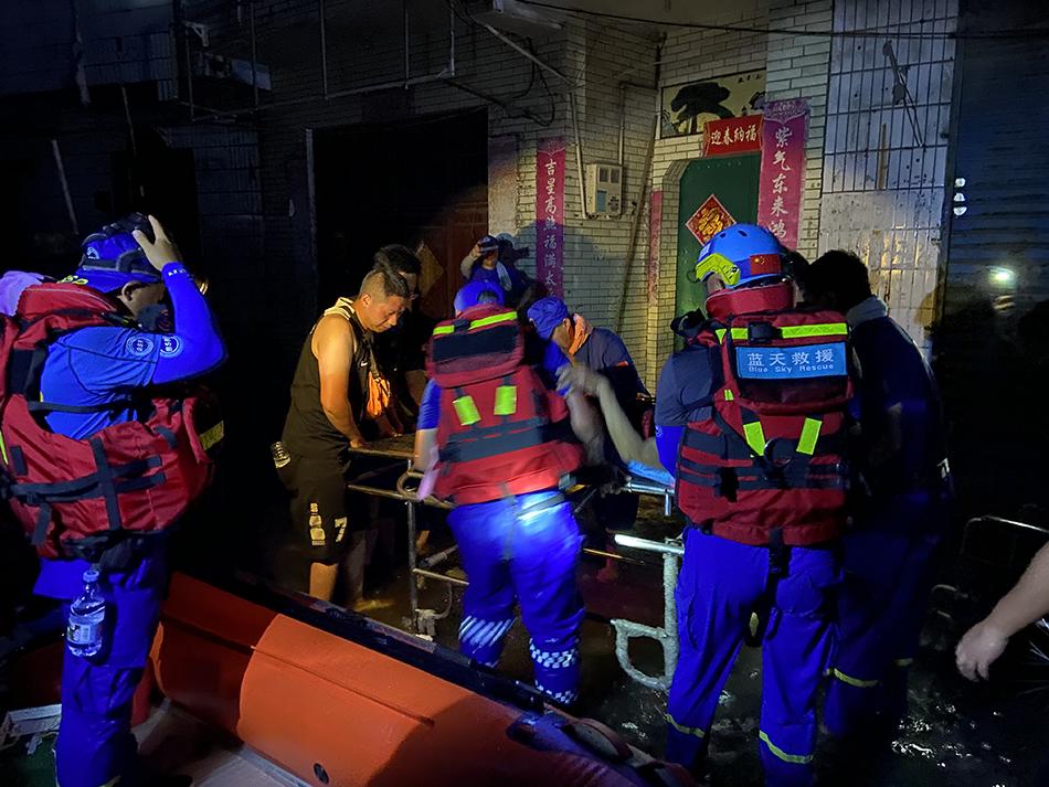 一名老人行动不便,救援人员用担架车将其小心翼翼送出。