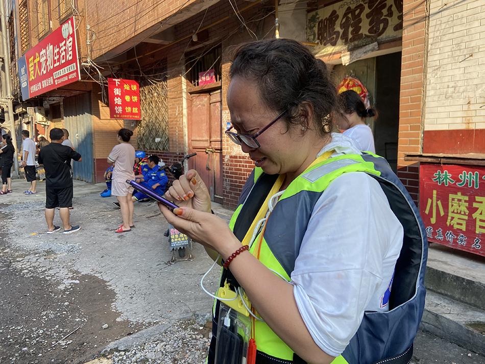 满开燕联络受灾居民、协调救援队员、疏散围观群众。个头不高的她在救援现场拥挤的人群中忙个不停。