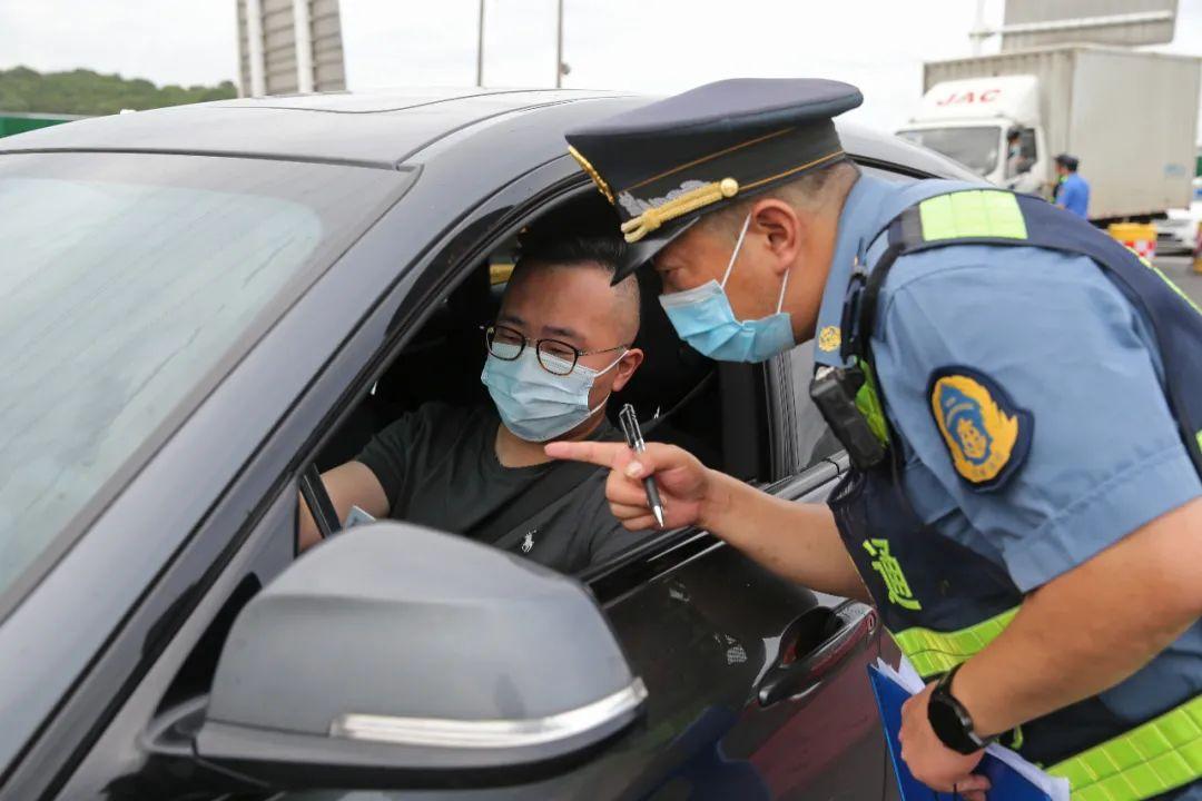 7月25日,南京沪蓉高速收费站出城方向,交警、城管、交通等部门开展联合工作,查验驾乘人员健康码和48小时内核酸检测阴性证明。