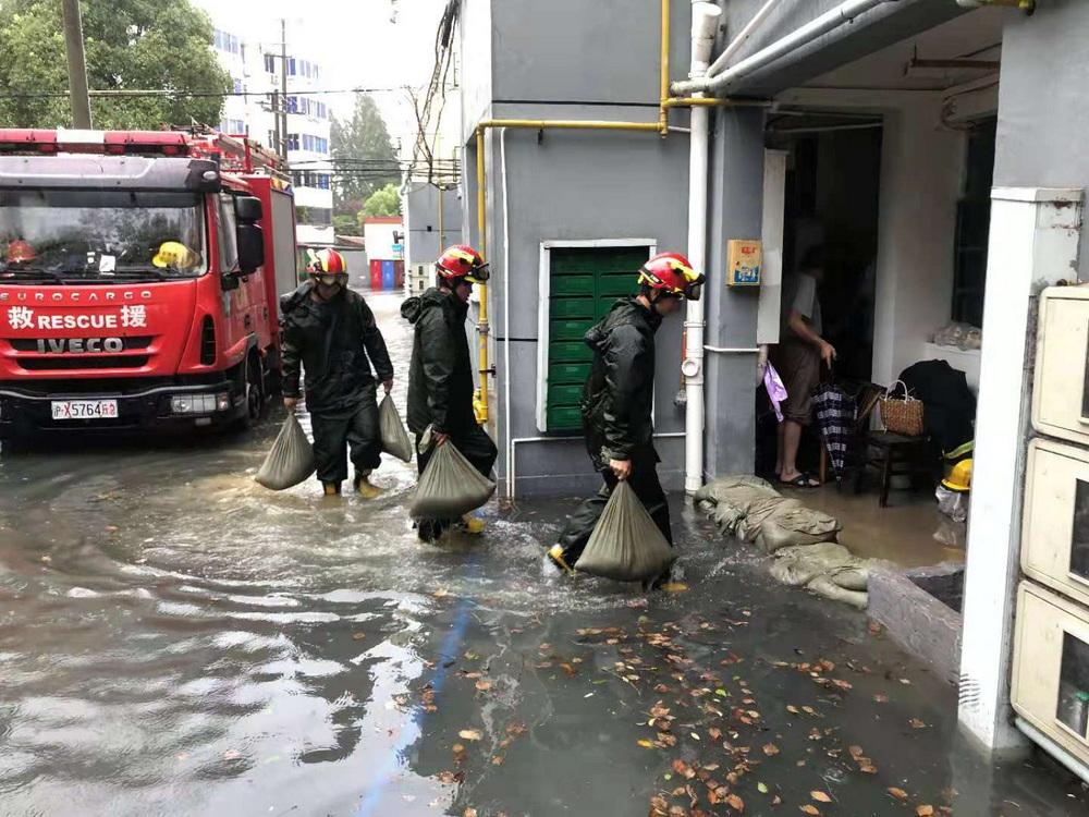 消防人员协助居委会,在地势低洼处铺设了沙袋,最大限度阻止积水蔓延。