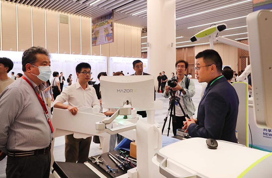2021年7月26日,第四届进博会部分展区展前供需对接会在上海举行,图为参展企业工作人员(右一)和参会嘉宾在展台前交流。 新华社记者 方喆 摄