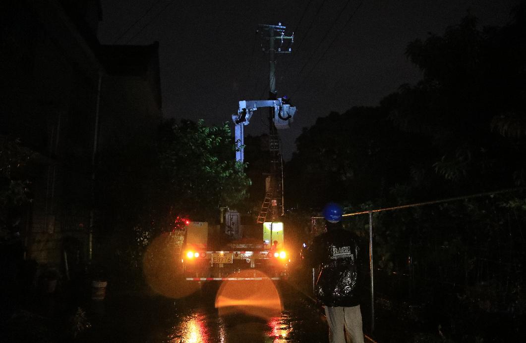 """受台风""""烟火""""影响,嘉定沁园别墅供电设施遭断裂树枝影响发生短路故障,国网上海嘉定供电公司员工冒着风雨进行抢修。"""