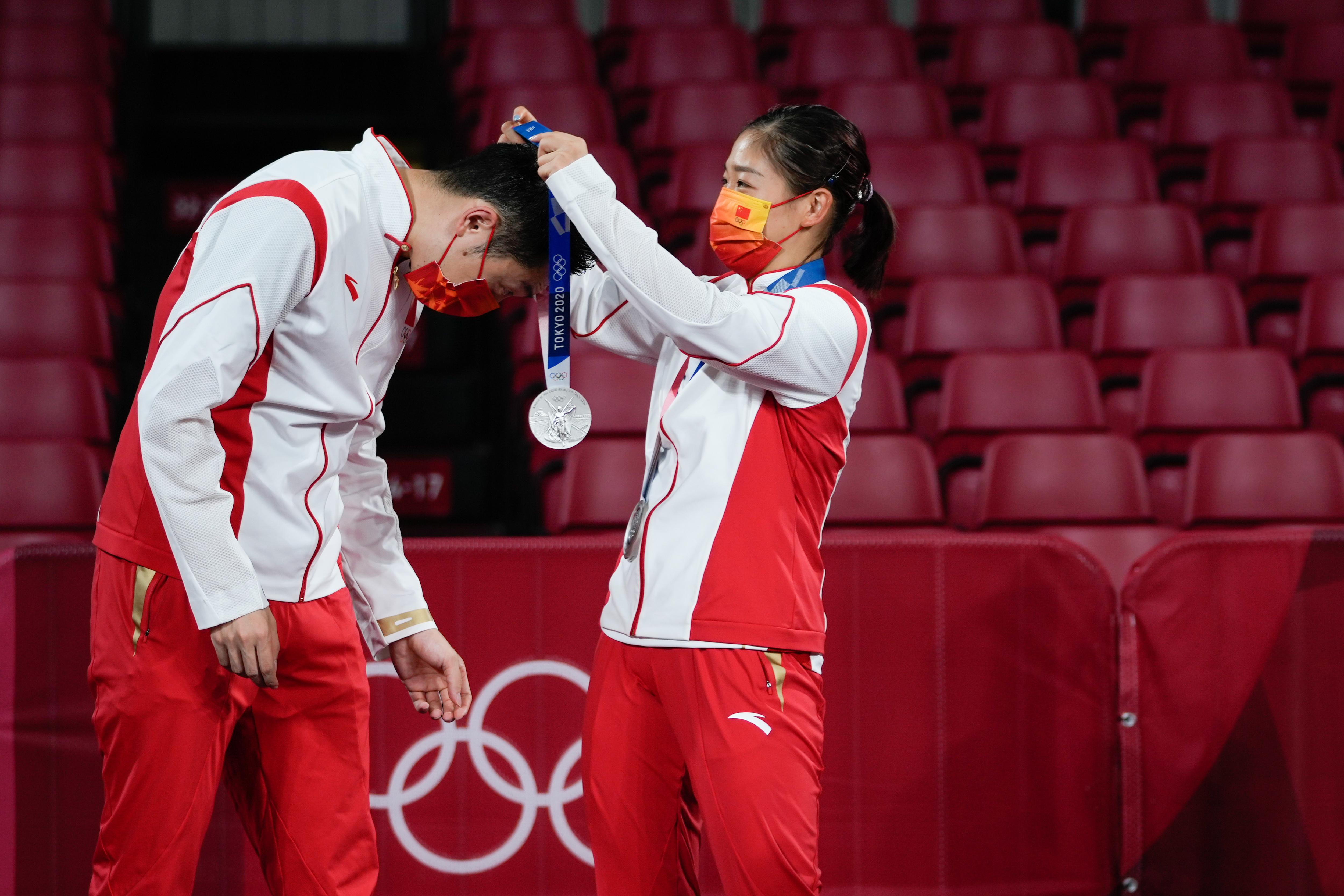 刘诗雯为许昕戴上银牌。