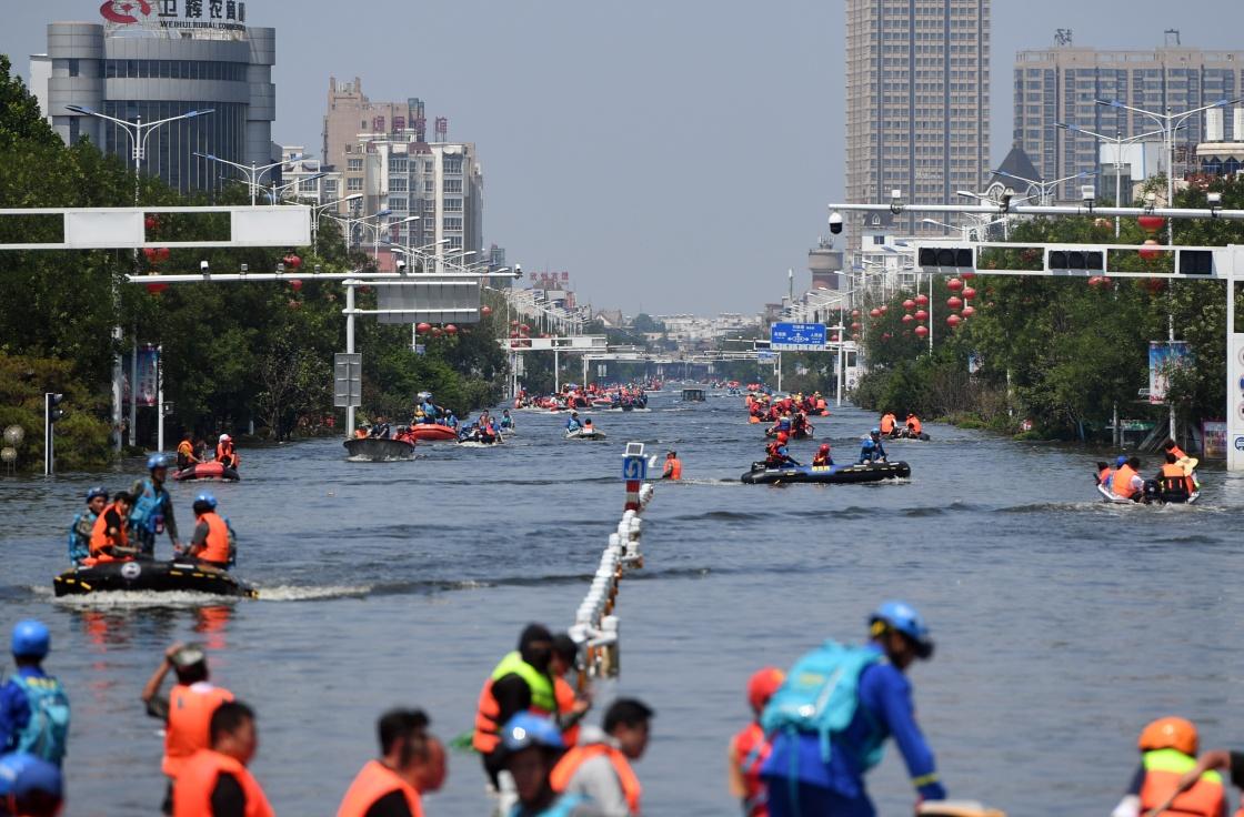 7月27日,在积水严重的卫辉城区,救援人员在搜救被困群众。新华社 图