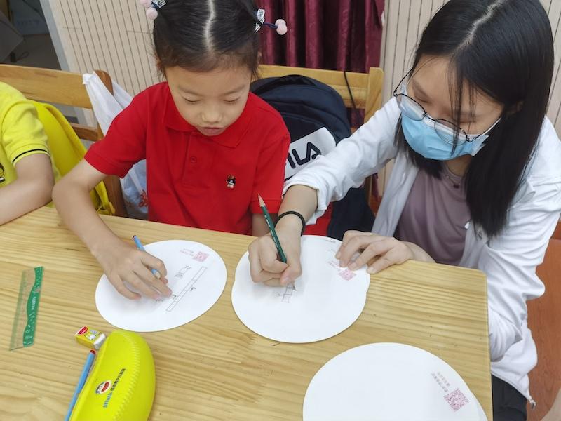 志愿者辅导小朋友作画。