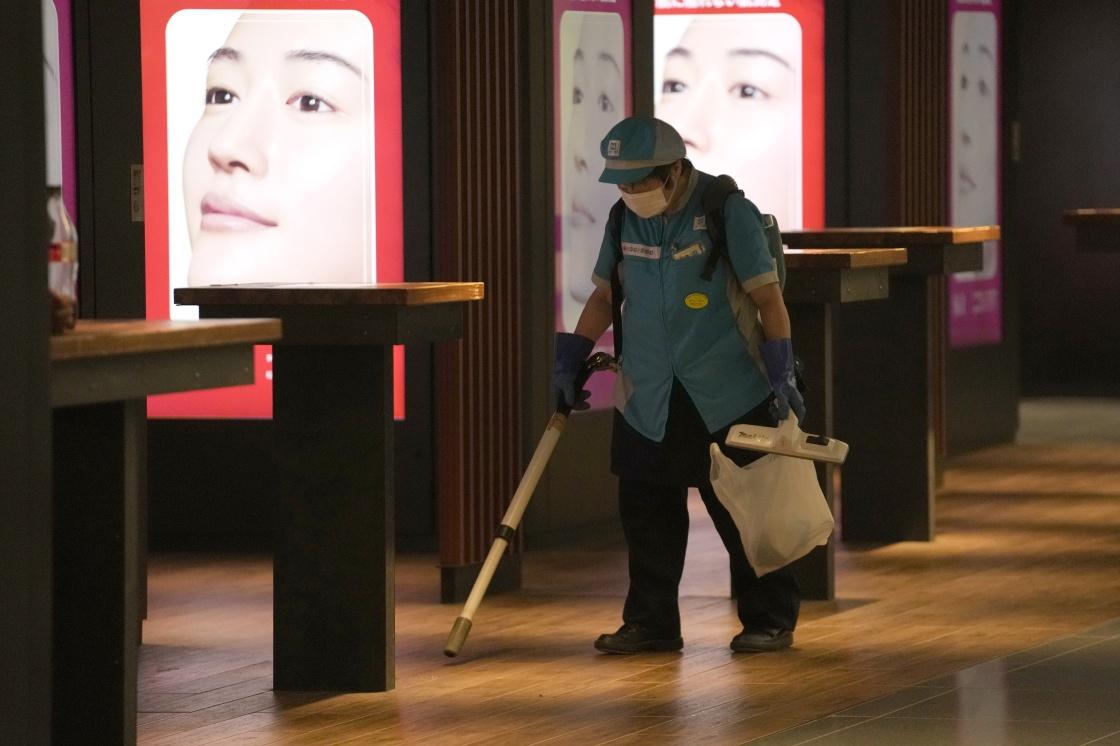 7月29日,一名戴着口罩的工作人员在日本东京一地铁站内清洁地面。 新华社 图