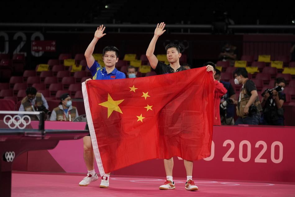 马龙(右)和樊振东在比赛后携手共展国旗