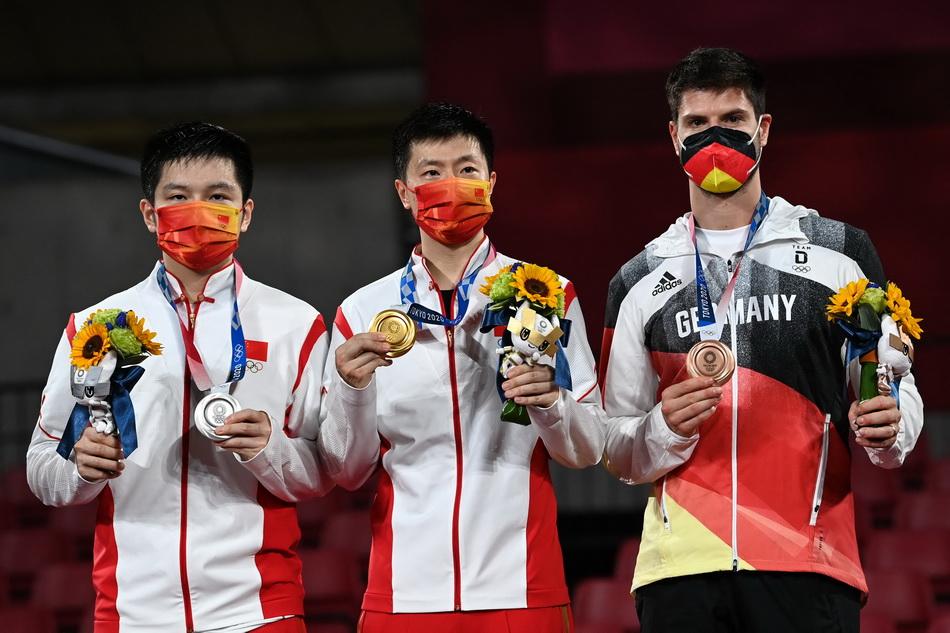 马龙(中)、樊振东和季军德国选手奥恰洛夫(右)