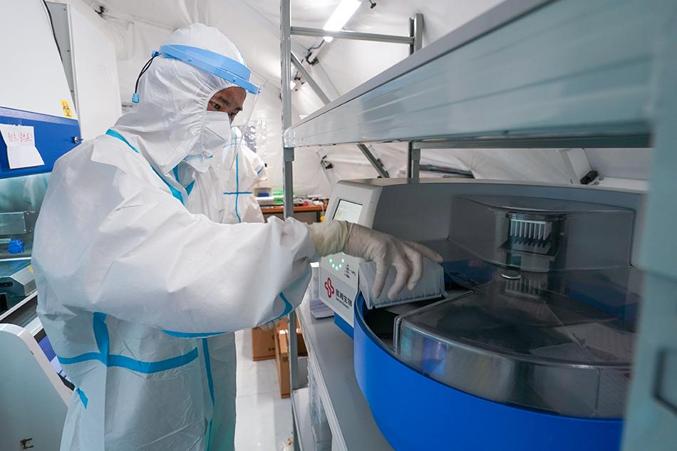 """7月27日,在位于南京青奥体育公园体育馆内的""""猎鹰号""""气膜实验室,工作人员在进行核酸提取作业。 新华社记者 李博 摄"""